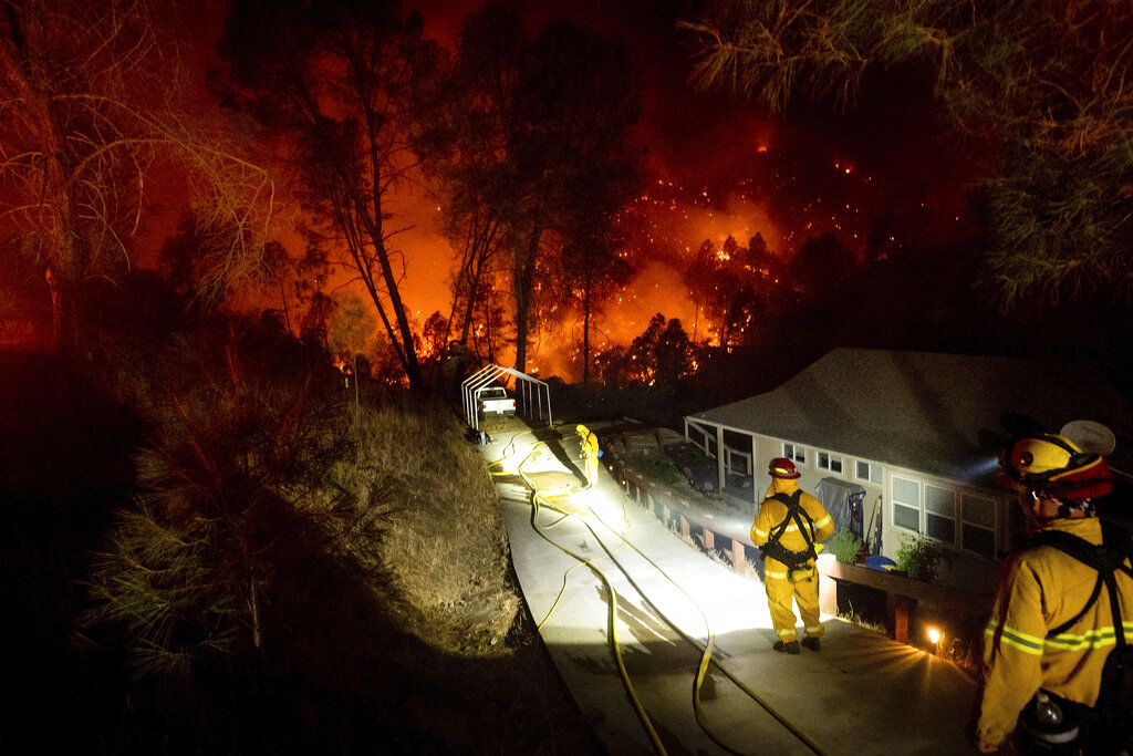 Firefighters protect a home in the Berryessa Estates neighborhood of unincorporated Napa County, Calif., as the LNU Lightning Complex fires burn on Aug. 21, 2020. (AP Photo/Noah Berger)