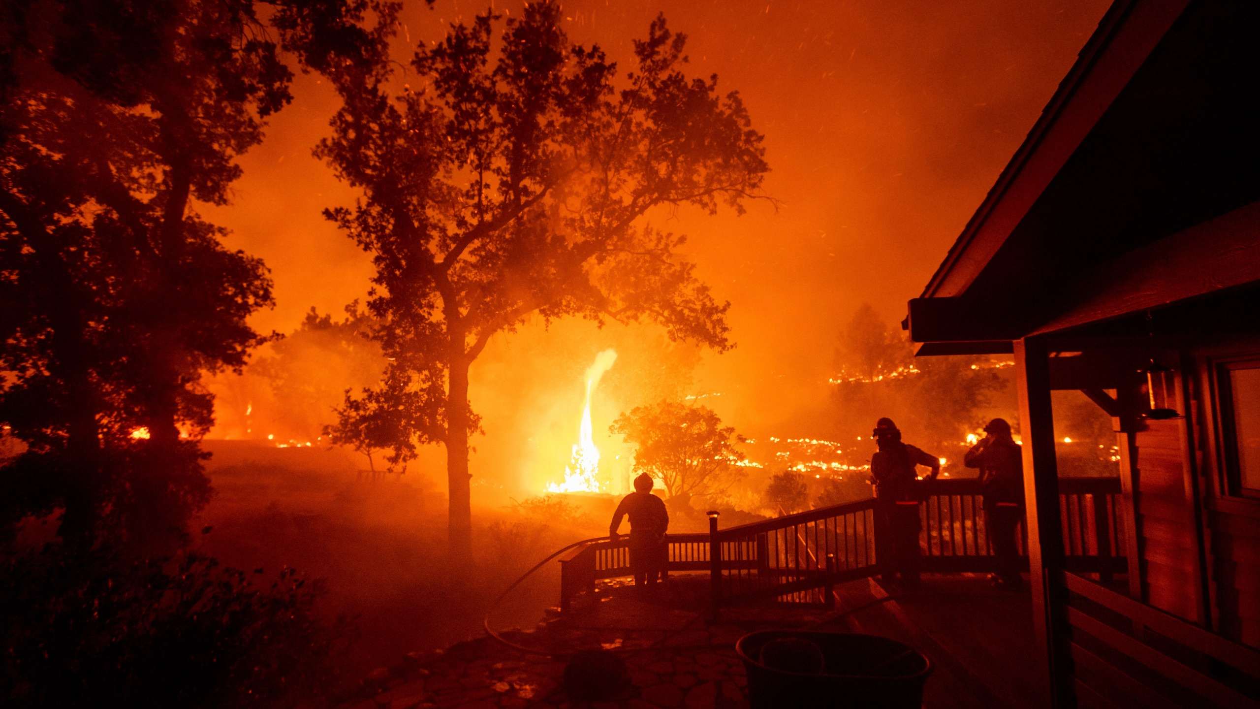 Firefighters watch flames from the LNU Lightning Complex fires approach a home in the Berryessa Estates neighborhood of unincorporated Napa County on Aug. 21, 2020. (AP Photo/Noah Berger)