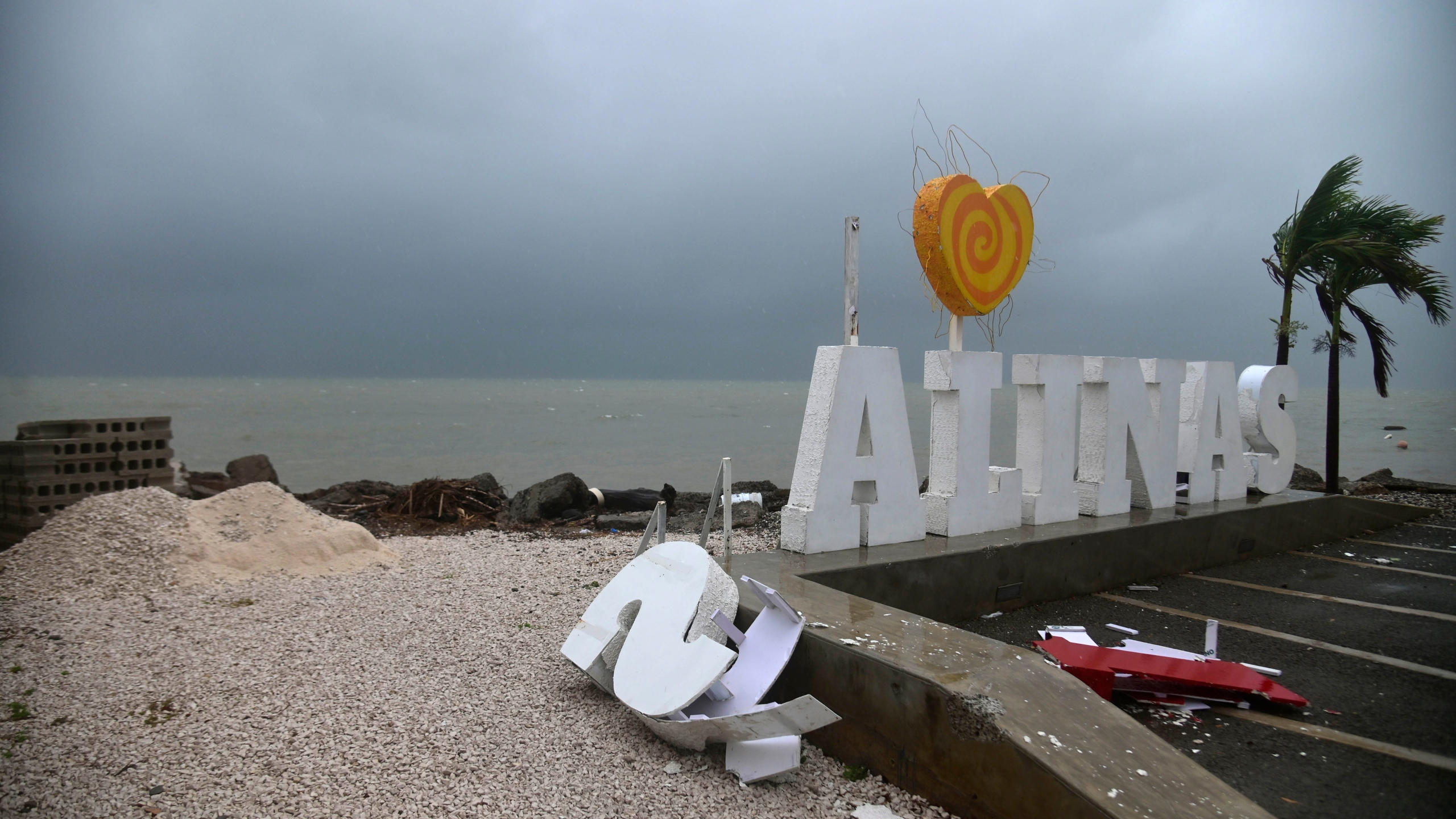 Remnants of a city sign lay on the beach damaged by Tropical Storm Laura in Salinas, Puerto Rico, on Aug. 22, 2020. (AP Photo/Carlos Giusti)