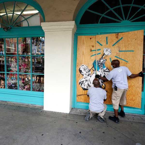 Workers board up shops in the French Quarter of New Orleans, on Aug. 23, 2020, in advance of Hurricane Marco, expected to make landfall on the Southern Louisiana coast. (AP Photo/Gerald Herbert)