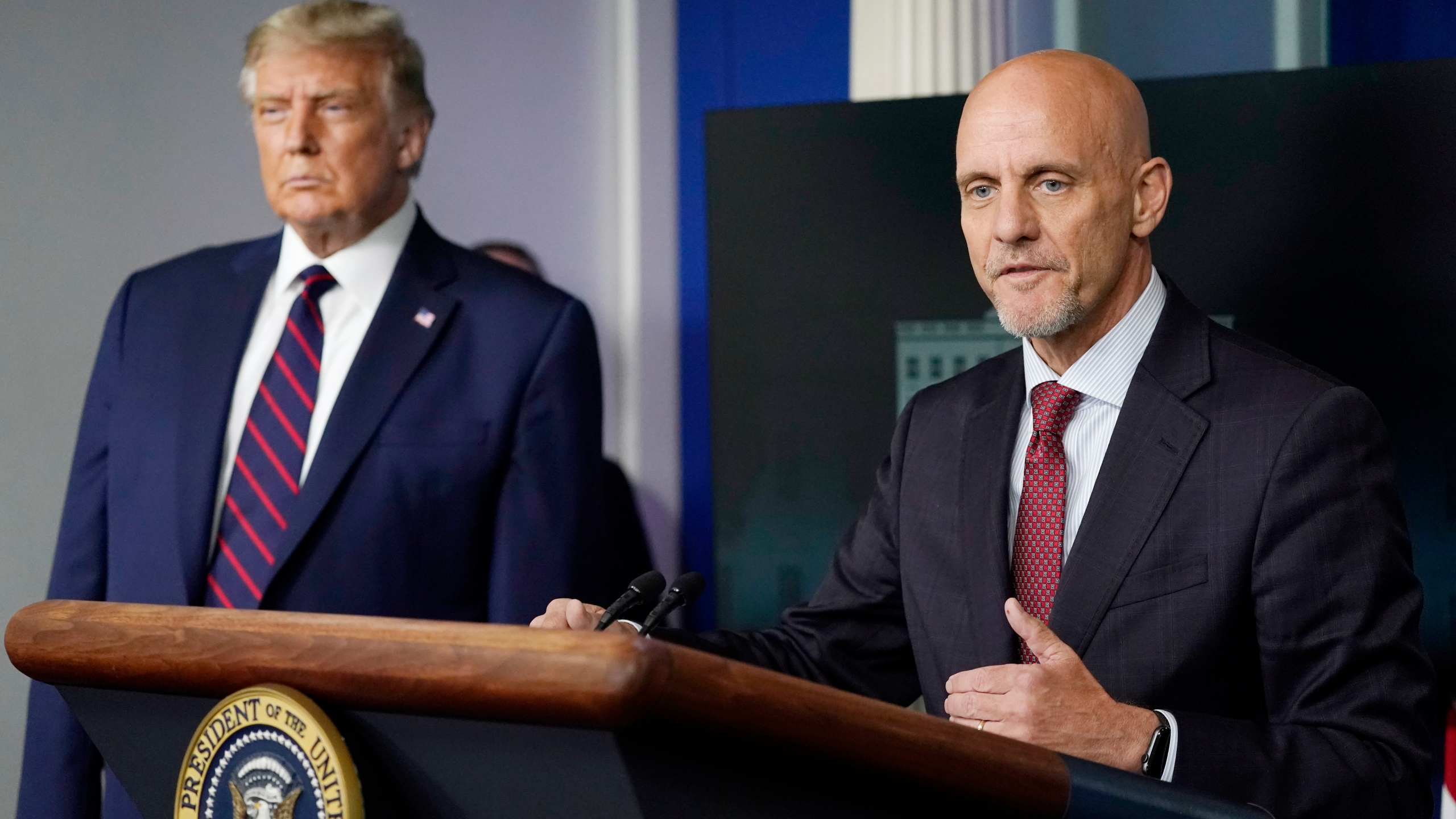 Donald Trump listens as Dr. Stephen Hahn, commissioner of the U.S. Food and Drug Administration, speaks during a media briefing in the James Brady Briefing Room of the White House, Sunday, Aug. 23, 2020, in Washington. (AP Photo/Alex Brandon)