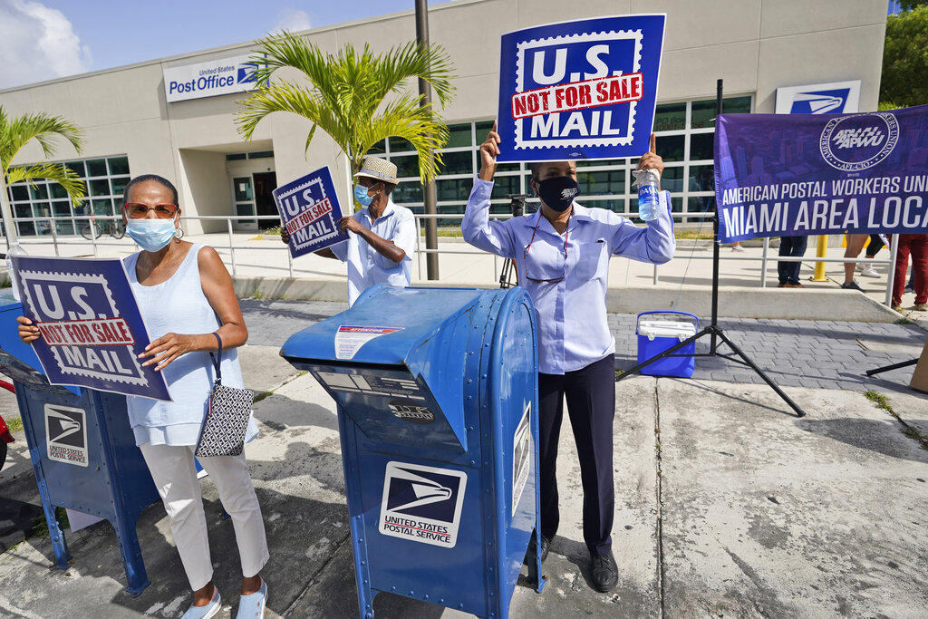 """Protesters demonstrate during a """"National Day of Action to Save the """"Peoples"""" Post Office!"""" outside the Flagler Station post office, Tuesday, Aug. 25, 2020, in Miami. (AP Photo/Wilfredo Lee)"""