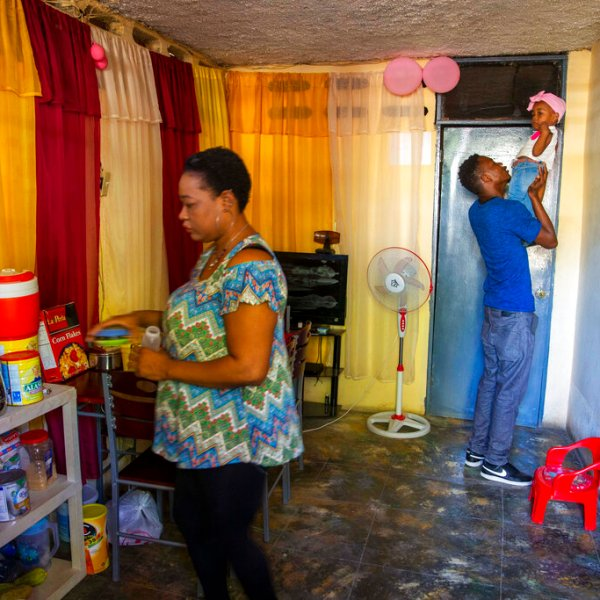 Verty plays with his 1-year-old daughter while his wife Saint Jean fixes the house in Port-au-Prince, Haiti, Tuesday, Aug. 25, 2020. (AP Photo/Dieu Nalio Chery)