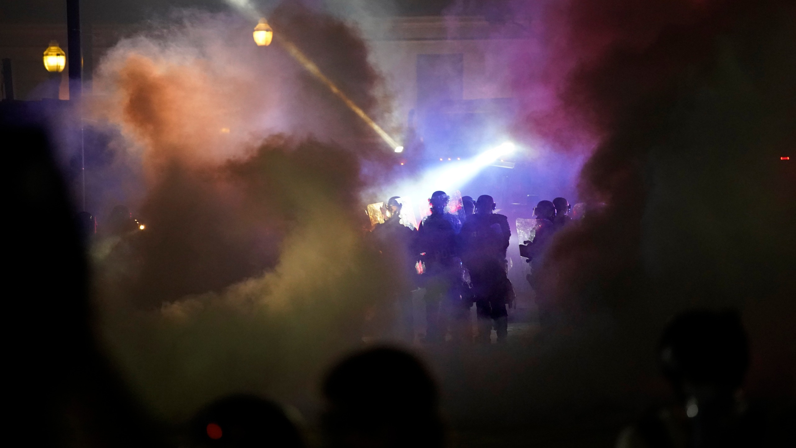 Police in riot gear clear the area in front of Kenosha County Courthouse in Wisconsin during clashes with protesters on Aug. 25, 2020. (David Goldman / Associated Press)