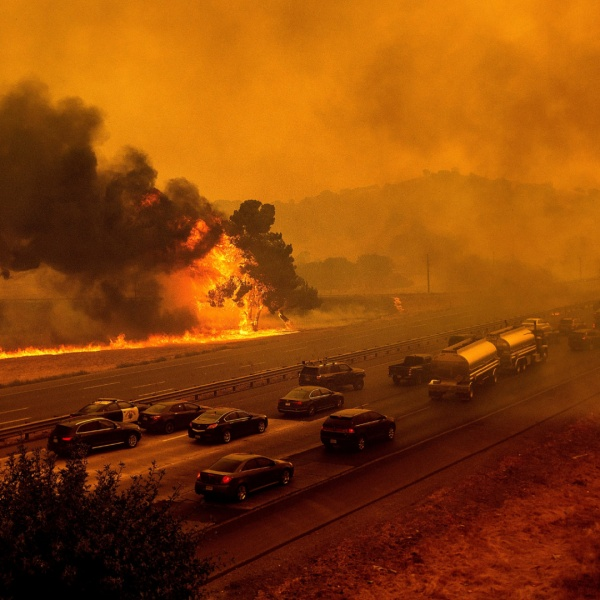 Flames from the LNU Lightning Complex fires jump Interstate 80 in Vacaville on Aug. 19, 2020. The highway was closed in both directions shortly afterward. (AP Photo/Noah Berger, File)