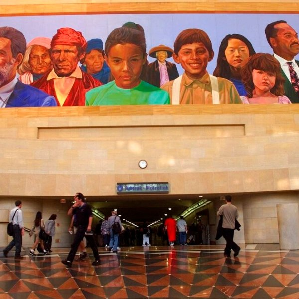 """In this Aug. 30, 2000, file photo, commuters walk into a tunnel at Union Station under the mural """"City of Dreams/River of History"""" by artist Richard Wyatt, showing the diversity of California's population. (AP Photo/Damian Dovarganes, File)"""