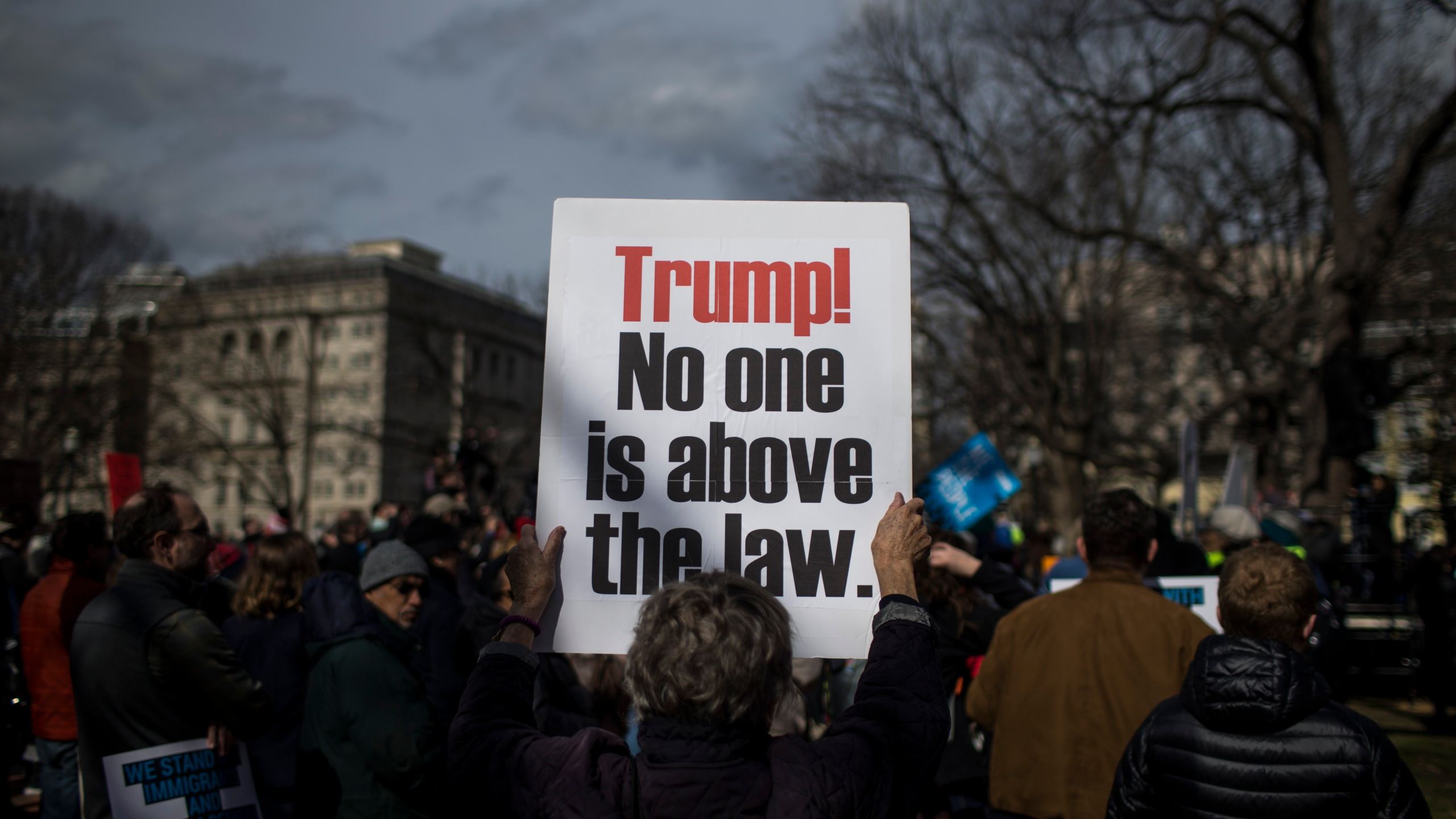 A demonstrator holds a sign in Lafayette Square during a demonstration organized by the American Civil Liberties Union (ACLU) protesting President Donald Trump's declaration of emergency powers on Feb. 18, 2019, in Washington, D.C. (Zach Gibson/Getty Images)
