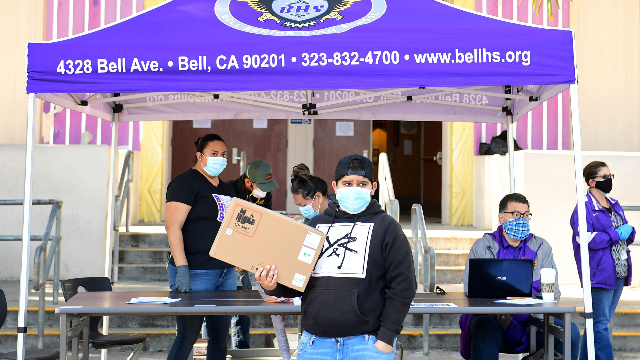 A student receives his laptop computer for remote learning which will be returned after the school year is over in front of Bell High School in Bell, California on April 15, 2020. (FREDERIC J. BROWN/AFP via Getty Images)