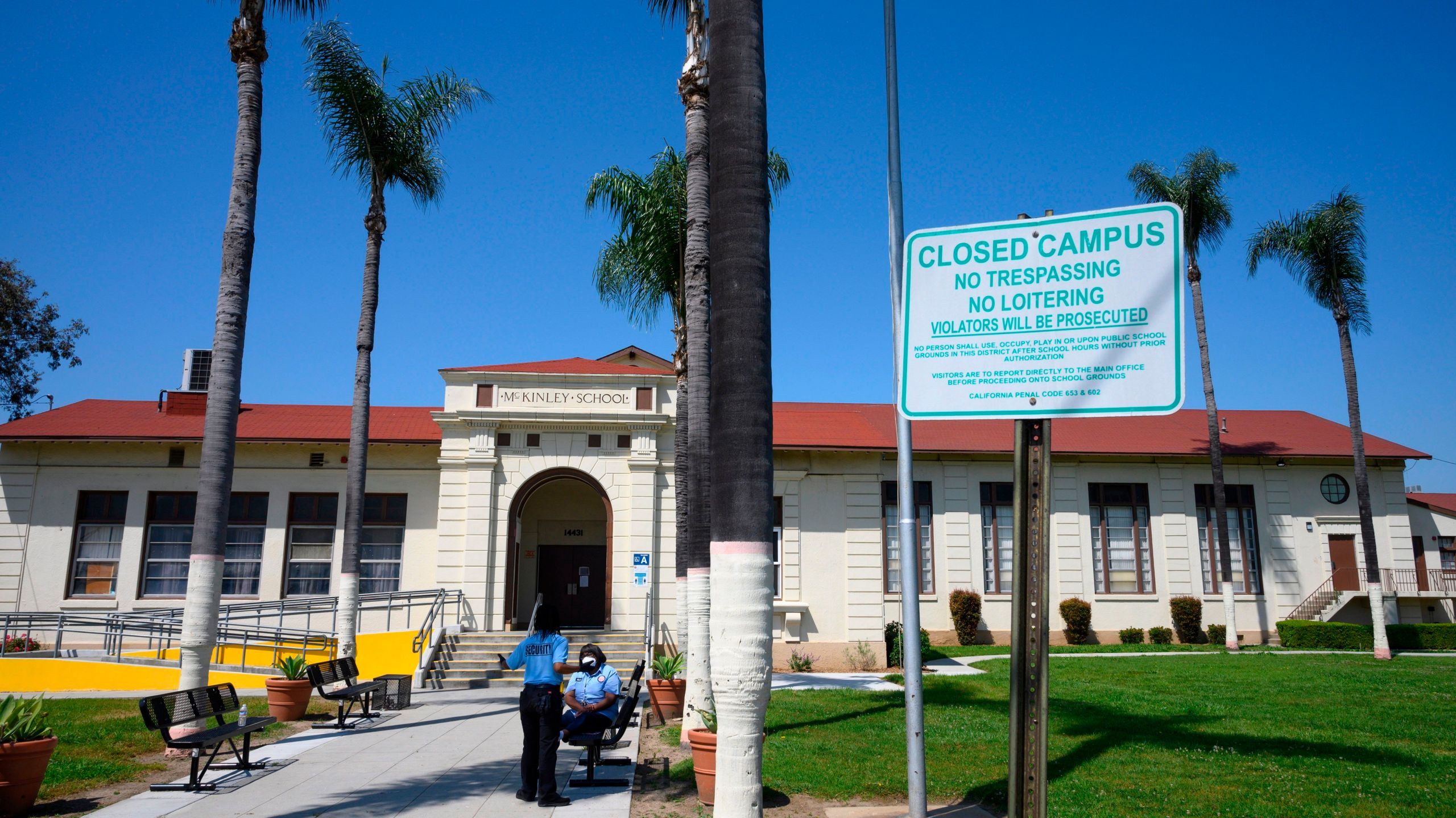 Two security guards talk on the campus of the closed McKinley School, part of the Los Angeles Unified School District (LAUSD) system, in Compton, California, just south of Los Angeles, on April 28, 2020. (ROBYN BECK/AFP via Getty Images)