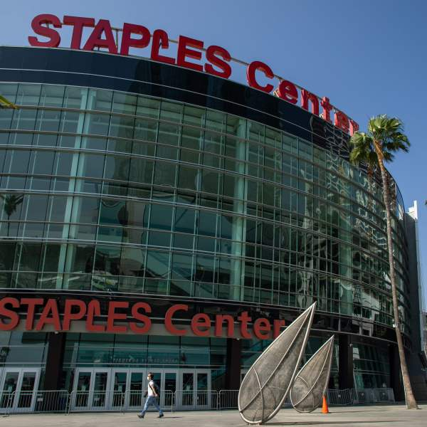 A man wearing a face mask walks in front of the Staples Center in downtown Los Angeles on May 9, 2020. (Apu Gomes / AFP via Getty Images)