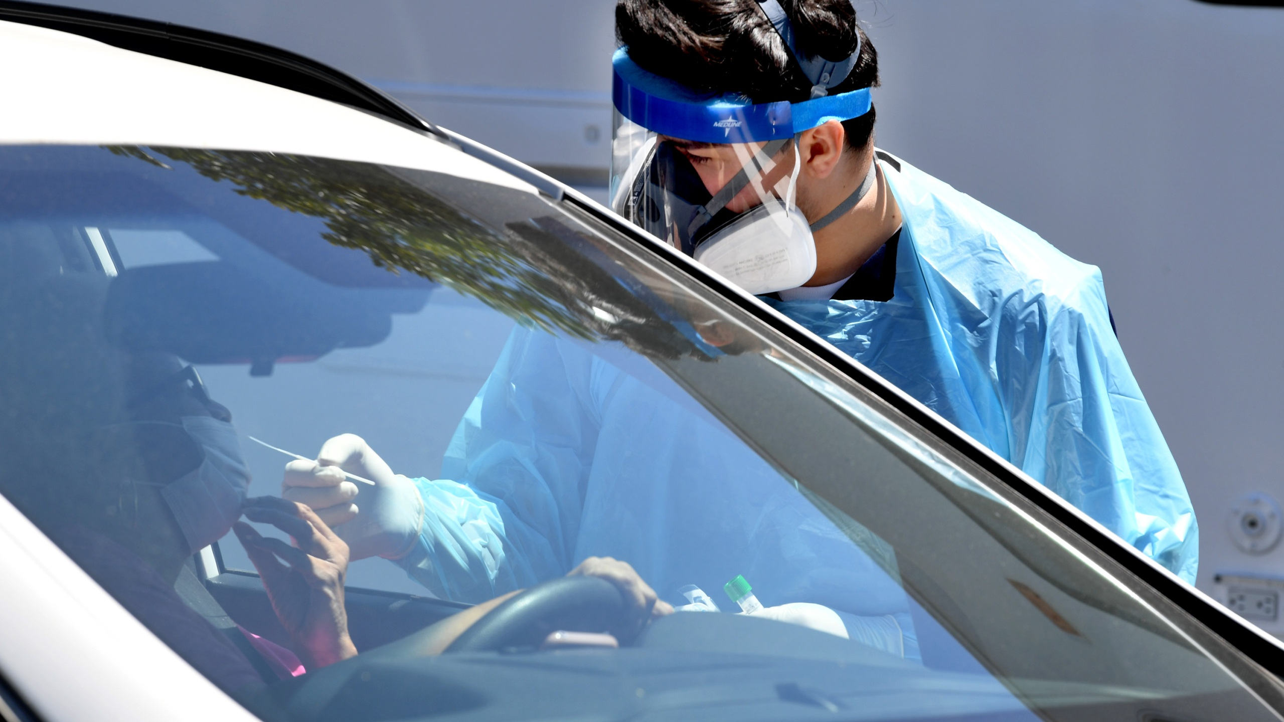 Workers wearing personal protective equipment (PPE) perform drive-up COVID-19 testing administered from a car at Mend Urgent Care testing site for the novel coronavirus at the Westfield Culver City on April 24, 2020 in the Culver City neighborhood of Los Angeles, California. (Kevin Winter/Getty Images)