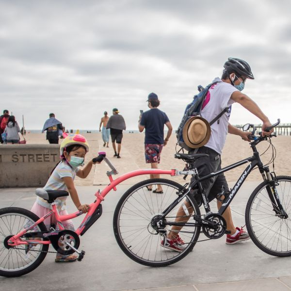 A girl and her father wear facemasks while they push their bikes in Hermosa Beach on July 14, 2020. (Apu GOMES / AFP via Getty Images)