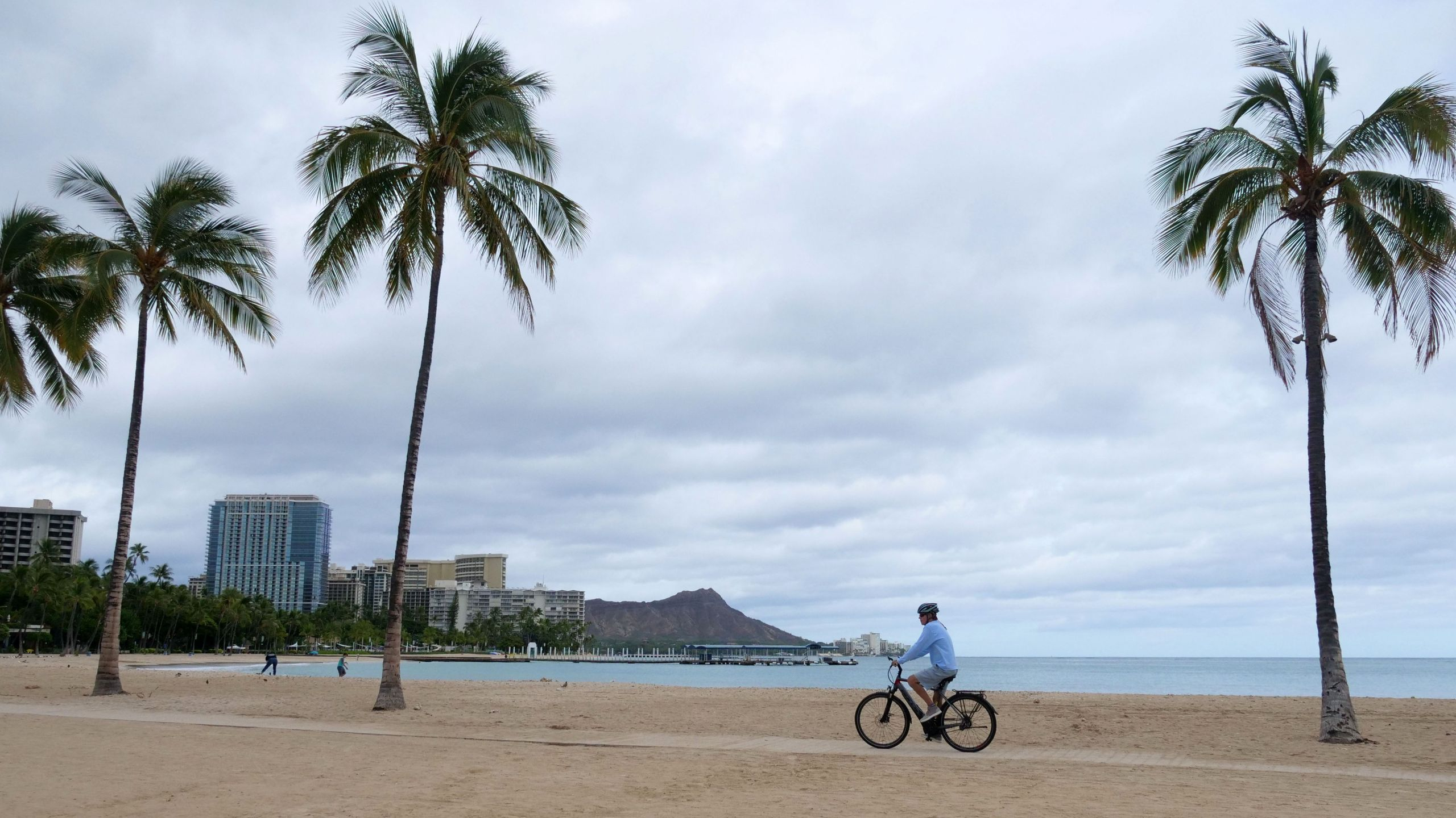 A cyclist rides along an empty Waikiki Beach on July 26, 2020. (RONEN ZILBERMAN/AFP via Getty Images)