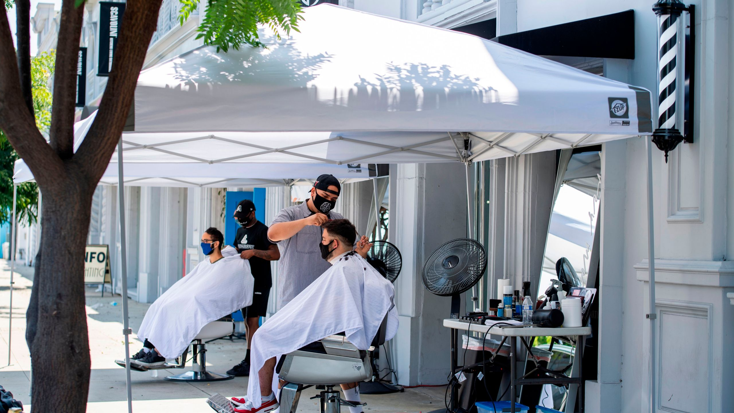 Stylists from Grey Matter LA cut clients' hair, at a distance on the sidewalk and while wearing facemasks on Aug. 4, 2020, in Los Angeles. (VALERIE MACON/AFP via Getty Images)