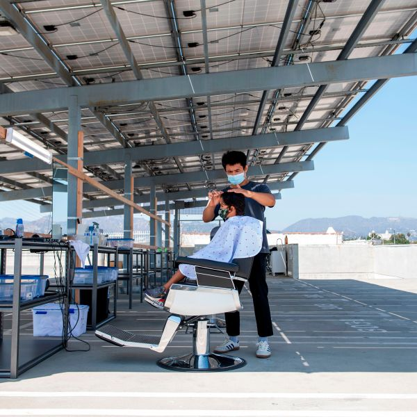 A stylist from Grey Matter LA cuts a young client's hair on a roof top parking lot amid the novel coronavirus pandemic, Aug. 4, 2020, in Los Angeles. (Valerie Macon / AFP / Getty Images)
