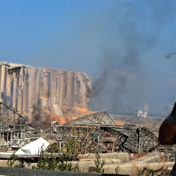 A man wearing a protective mask against the coronavirus stands across the road from the damaged grain silos of Beirut's harbour August 5, 2020, one day after a powerful twin explosion tore through Lebanon's capital, resulting from the ignition of a huge depot of ammonium nitrate at the city's main port. (STR/AFP via Getty Images)