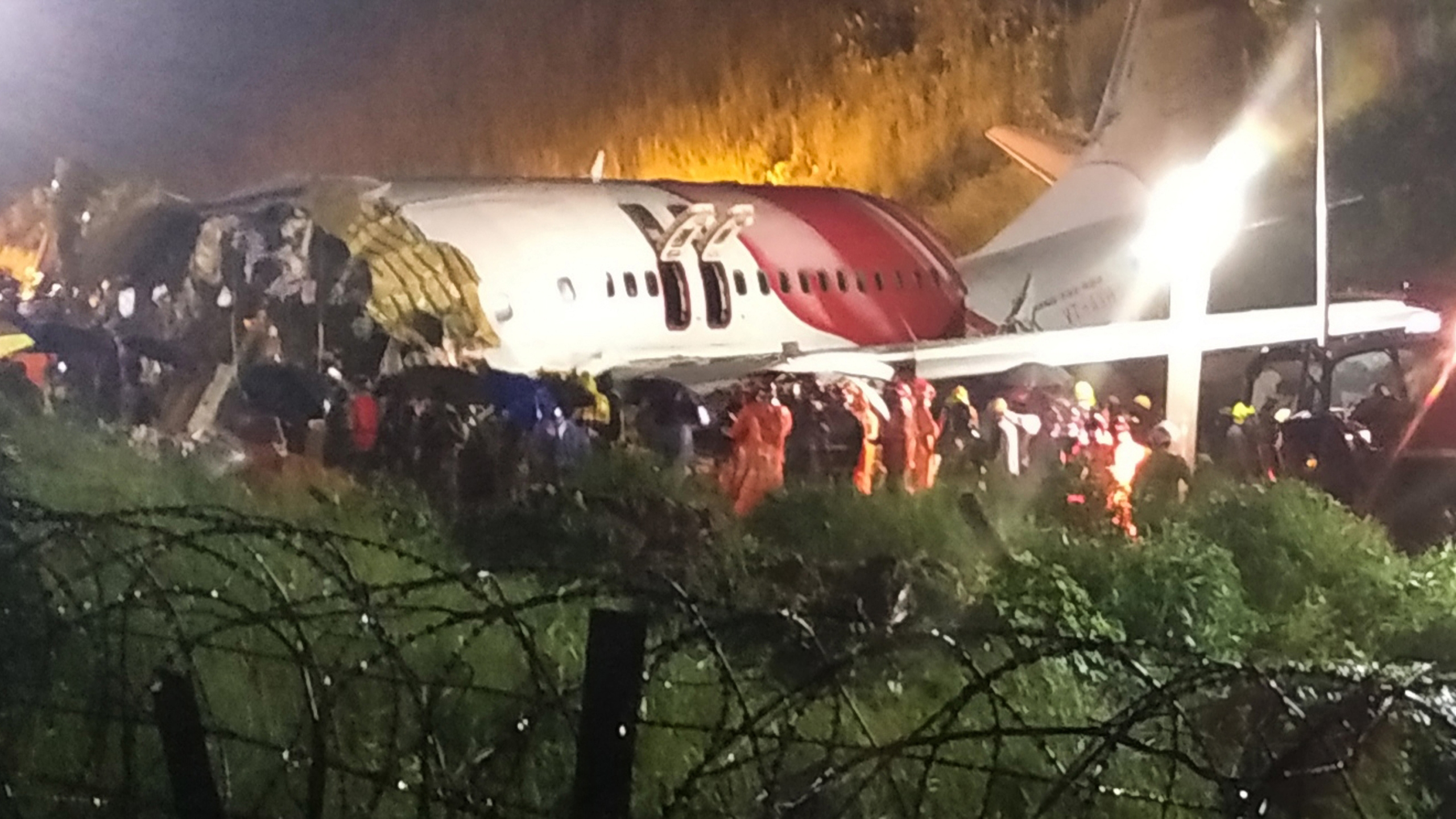 First responders gather around the wreckage of an Air India Express jet, which was carrying more than 190 passengers and crew from Dubai, after it crashed by overshooting the runway at Calicut International Airport in Karipur, Kerala, on August 7, 2020. (AFP via Getty Images)