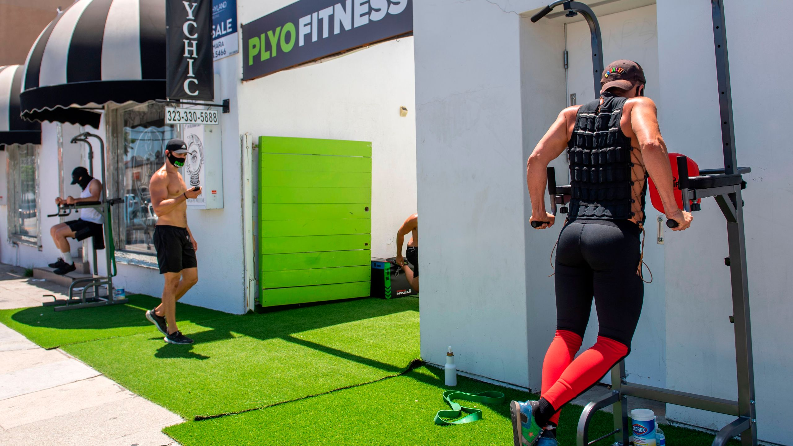 People take an outdoor class at Pylo Fitness, with workout equipment set up on the sidewalk on La Brea Blvd, on Aug. 7 2020, in Los Angele. (VALERIE MACON/AFP via Getty Images)