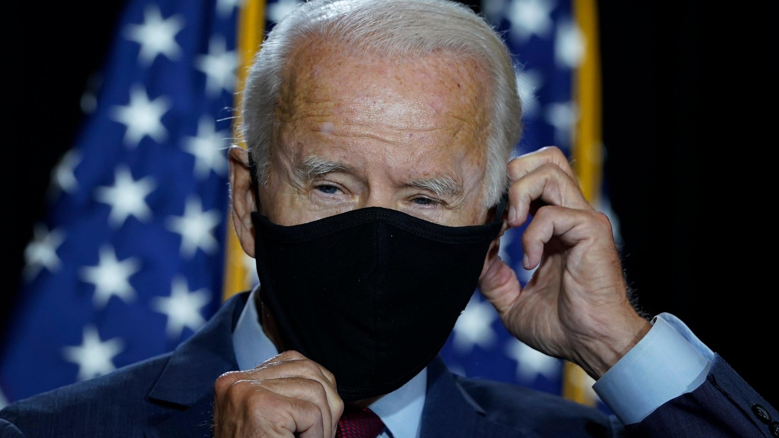 Presumptive Democratic presidential nominee former and Vice President Joe Biden puts his mask back on after delivering remarks following a coronavirus briefing with health experts at the Hotel DuPont on Aug. 13, 2020 in Wilmington, Delaware. (Drew Angerer/Getty Images)