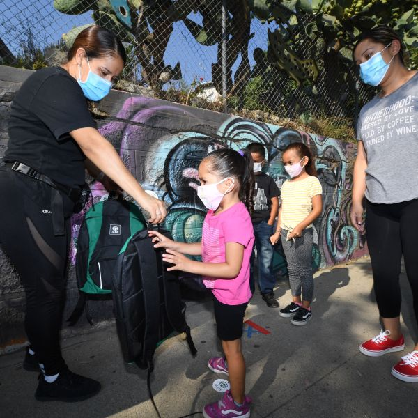 A volunteer hands 3-year-old Zayla a backpack filled with school supplies at a distribution to support neighborhood families as her mom Claudia Rodriguez, right, looks on, Aug. 14, 2020 in Los Angeles. (ROBYN BECK/AFP via Getty Images)