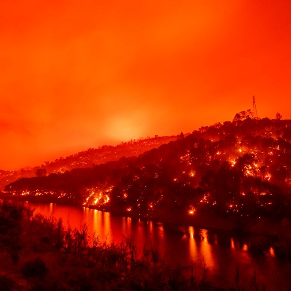 In this long exposure photograph, flames set ablaze both sides of a segment of Lake Berryessa during the Hennessey fire in the Spanish Flat area of Napa on Aug. 18, 2020. (JOSH EDELSON/AFP via Getty Images)