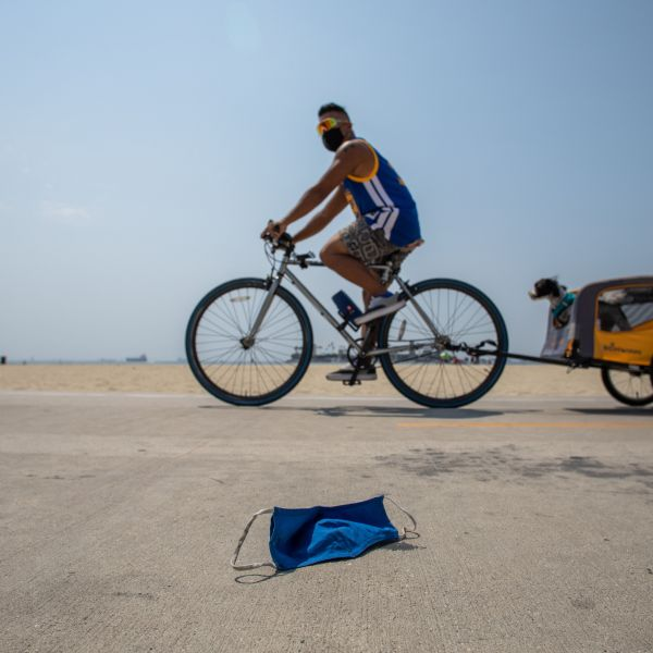 A man wearing a face mask rides his bike next to a discarded face mask in the bike path in Long Beach on Aug. 22, 2020.(APU GOMES/AFP via Getty Images)