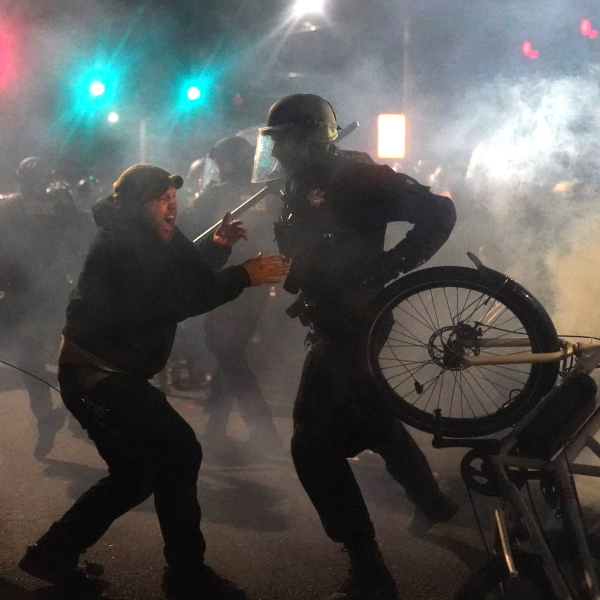 A Portland police officer rips a bike from the hands of a protester while dispersing a crowd from in front of the Multnomah County Sheriffs Office on Aug. 22, 2020, in Portland, Oregon. (Nathan Howard/Getty Images)