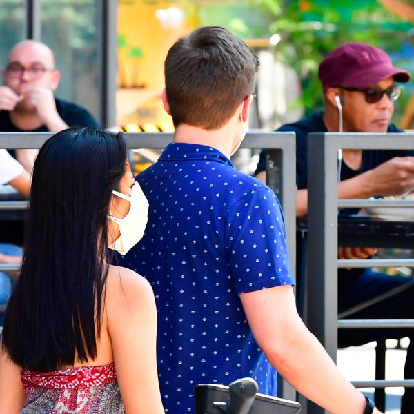 A pedestrian wears a face mask while walking past people dining outdoors in Los Angeles on Aug. 25, 2020. (FREDERIC J. BROWN/AFP via Getty Images)