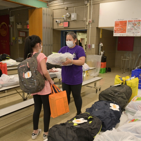 School teacher Melissa Wong hands belongings left behind before schools were shut down to a student who just graduated at Yung Wing School P.S. 124 on June 29, 2020 in New York City. ( Michael Loccisano/Getty Images)