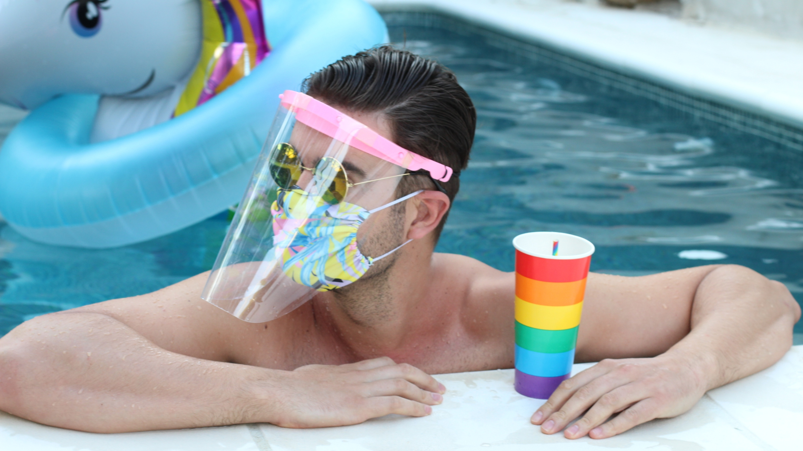 A man wearing a face mask and shield is seen in a swimming pool. (Getty Images)