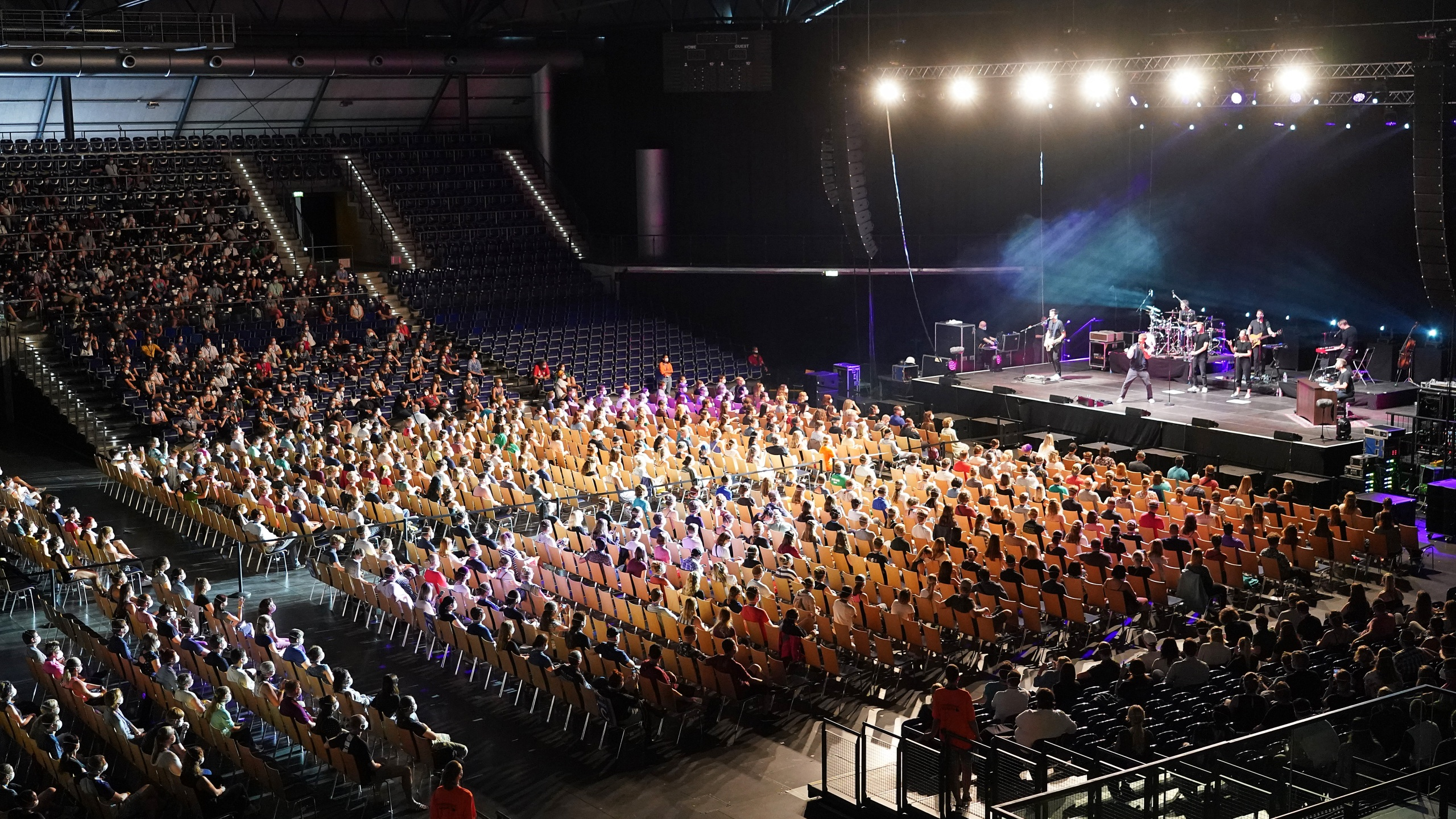 Participants wearing protective face masks watch singer Tim Bendzko perform in the RESTART-19 Covid transmission risk assessment study in a concert setting at an indoor arena during on Aug. 22, 2020, in Leipzig, Germany. (Sean Gallup/Getty Images)