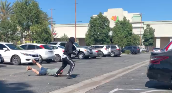 A screenshot from a video taken by a bystander shows a man being robbed in Huntington Park on July 30, 2020.