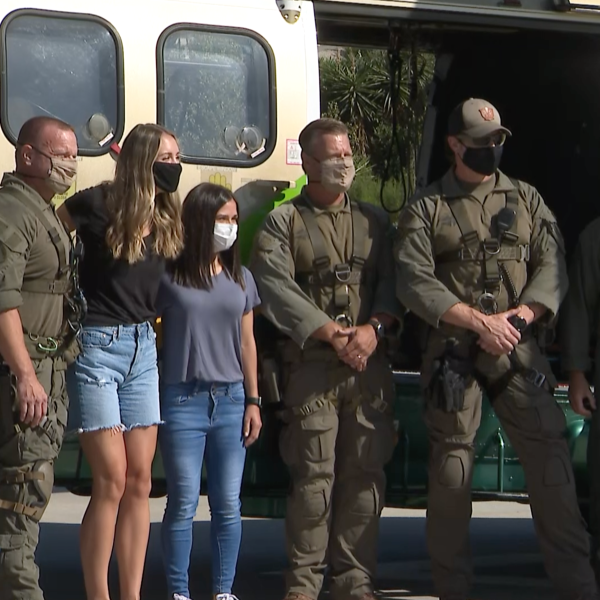 Deputies assigned to the Special Enforcement Bureau and Aero Bureau meet with two women they rescued on Aug. 8, 2020 in East Los Angeles. (KTLA)