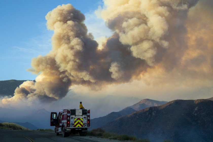 A firefighter from Carpinteria monitors a huge plume of smoke from the Apple north of Banning in this undated photo. (Gina Ferazzi / Los Angeles Times)