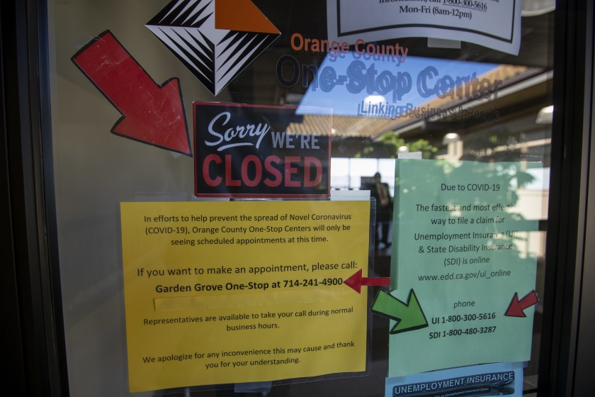 Signs are posted in May on the doors of the Orange County One-Stop Center in Garden Grove, which provides employment and training services.(Allen J. Schaben / Los Angeles Times)