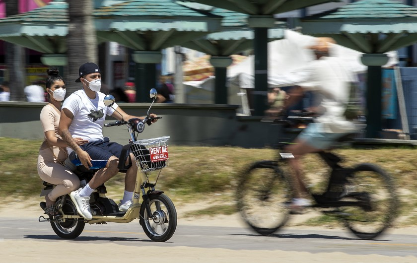 People wear protective masks while riding on the bicycle path in Venice Beach on Sunday.(Mel Melcon / Los Angeles Times)