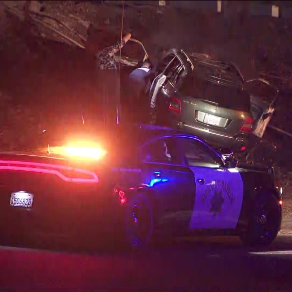 One person died when a car crashed into a tree and caught fire on a freeway embankment in Azusa on Aug,21, 2020.(KTLA)