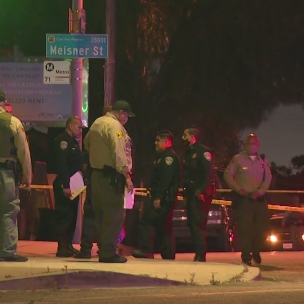 Investigators stand at the scene of a deadly crash in East L.A., where an L.A. Metro bus fatally struck a man. (RMG News)