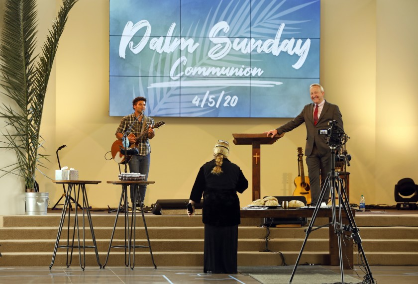 Pastor Rob McCoy, right, gives Communion at an April 5 Palm Sunday service at his Thousand Oaks church, Godspeak Calvary Chapel. (Carolyn Cole / Los Angeles Times)