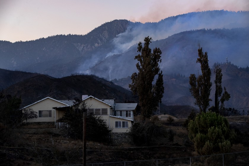 Scorched terrain surrounds a home off Bluff Street as the Apple fire smolders in the background on Tuesday in Banning, Calif.(Gina Ferazzi/Los Angeles Times)