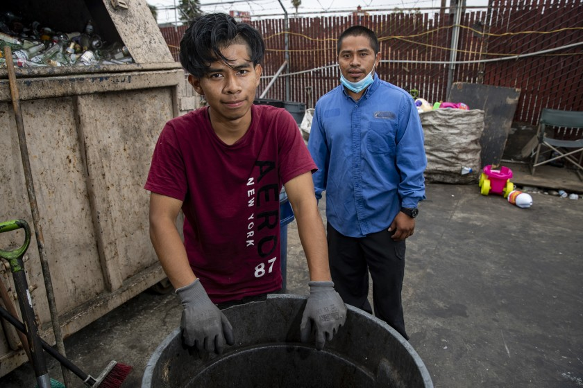 Gadseel Quiñonez, 29, right, and his brother Jose Quiñonez, 18, at the recycling center where they work in this 2020 photo. (Brian van der Brug / Los Angeles Times)
