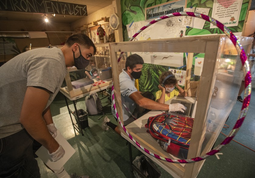 Kindergartner Jameson Miniex, 5, works with facilitator Kyle Fetter, left, and Star Education Director John Gaxiola inside his protective, learning pod at Eco Station in Culver City.(Mel Melcon / Los Angeles Times)