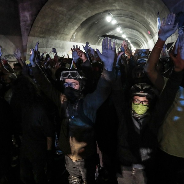 Protesters raise their hands as they're met by police at the 3rd Street tunnel in downtown Los Angeles on Aug. 26, 2020.(Robert Gauthier / Los Angeles Times)