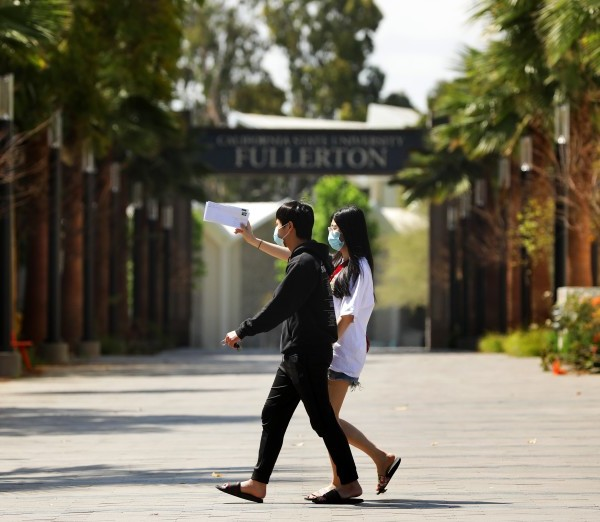 Cal State Fullerton student Linh Trinh, 21, right, and boyfriend Tan Nguyen, 21, walk around the deserted campus in April 2020. (Christina House / Los Angeles Times)