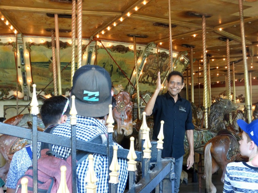 Julio Gosdinski welcomes riders to the Griffith Park carousel, where he worked for three decades, in this undated photo. (Kathryn Louyse via L.A. Times)