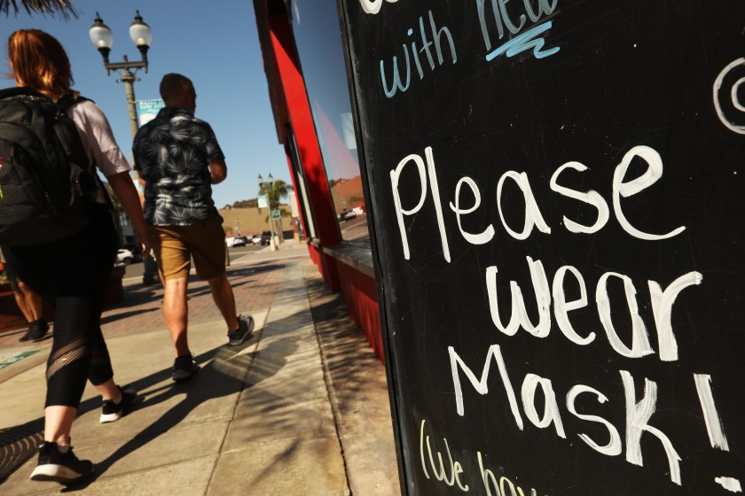 "Some restaurateurs in Mammoth Lakes, part of Mono County, believe they have been scapegoated because of state snafus in monitoring coronavirus cases. Above, a ""Please Wear Mask"" reminder in Huntington Beach. (Genaro Molina / Los Angeles Times)"