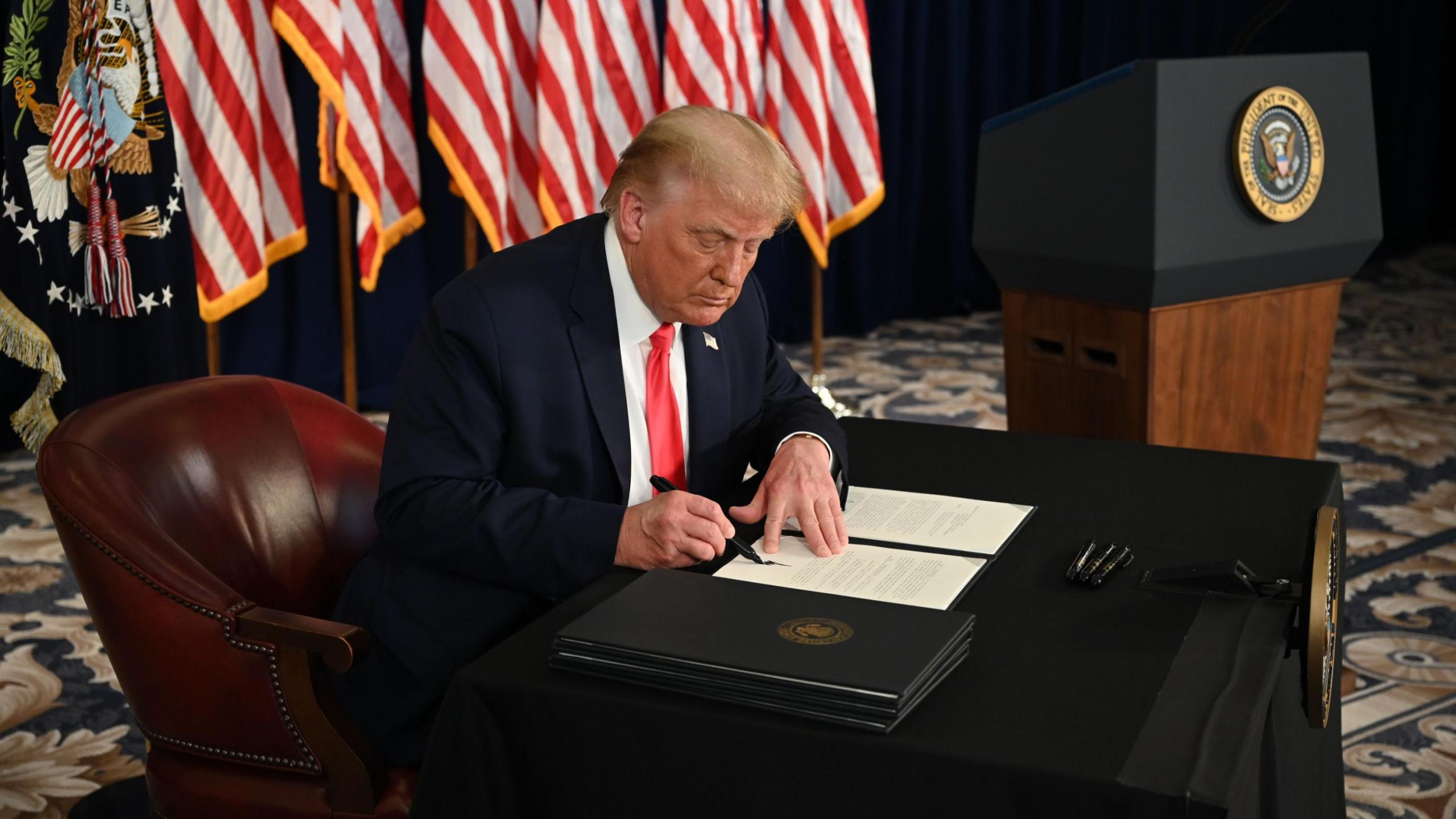 President Donald Trump signs executive orders extending coronavirus economic relief, during a news conference in Bedminster, New Jersey, on Aug. 8, 2020. (JIM WATSON/AFP via Getty Images)