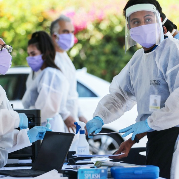 Health. are workers, wearing personal protective equipment (PPE), facilitate tests at a drive-in coronavirus (COVID-19) testing center at M.T.O. Shahmaghsoudi School of Islamic Sufism on August 11, 2020 in Los Angeles. (Mario Tama/Getty Images)