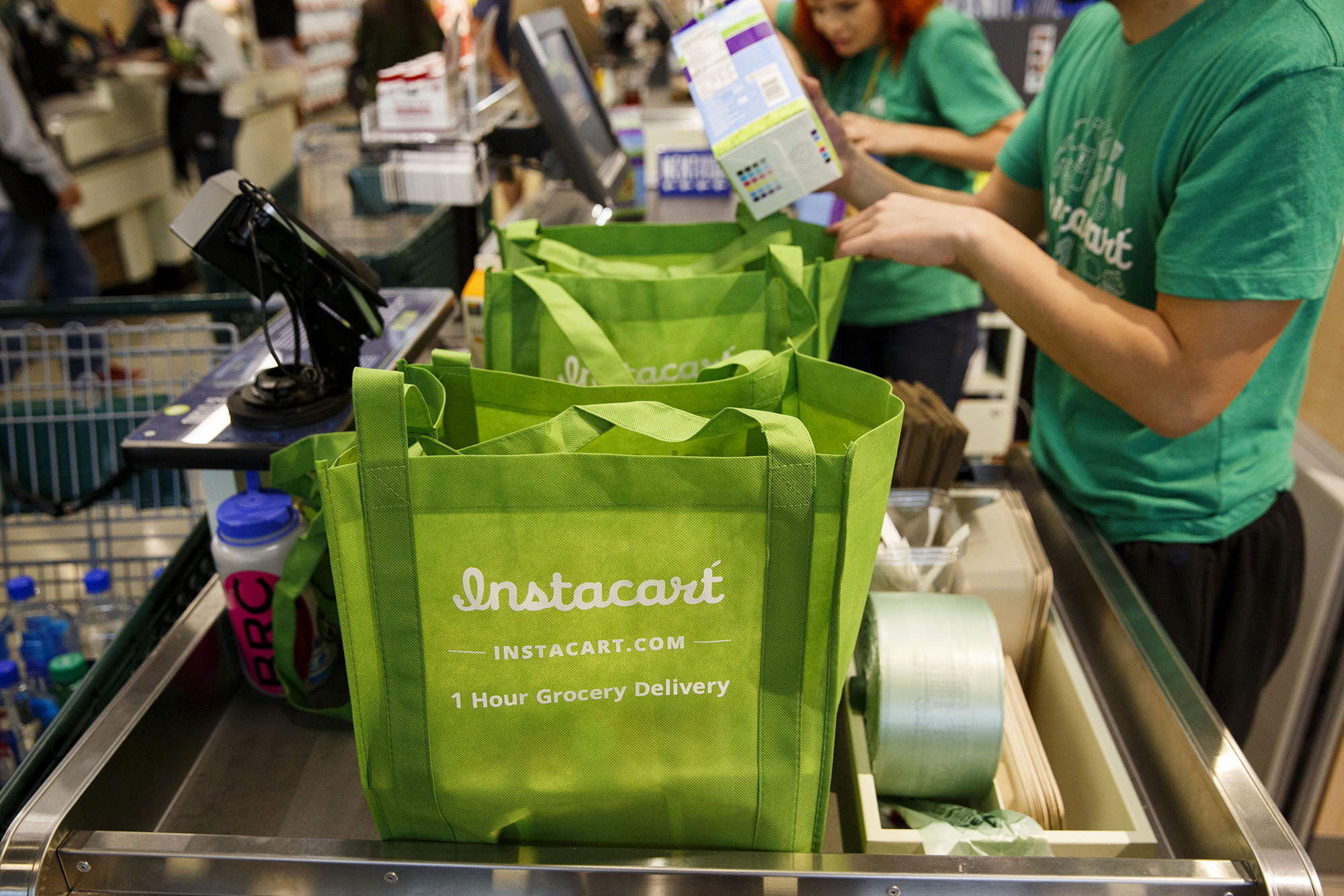 InstaCart employees fulfill orders for delivery at a Whole Foods Market Inc. store in downtown Los Angeles on Nov. 9, 2015. (Patrick T. Fallon/Bloomberg via Getty Images via CNN)