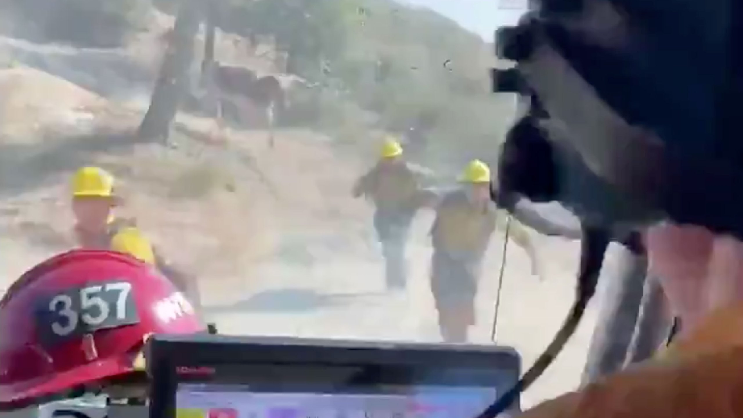 A screenshot from a video tweeted by the Ventura County Fire Department on Aug. 14, 2020 shows firefighters running away from a bull while responding to the Lake Fire in northwest L.A. County.
